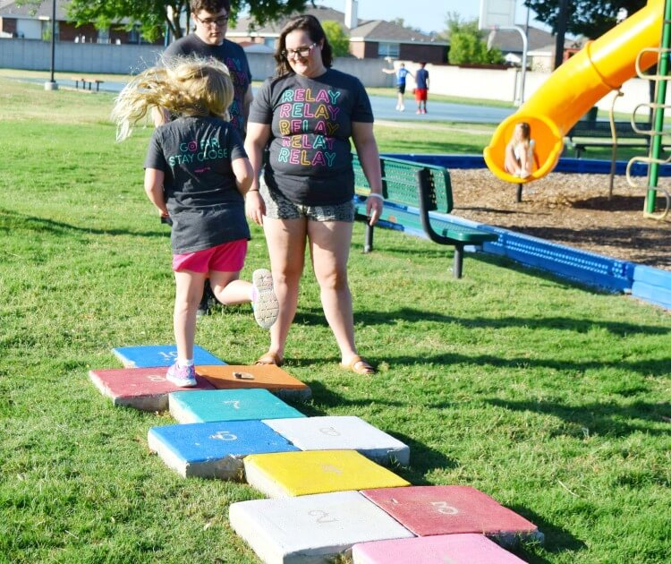 Big sister teaching little sister how to play Hopscotch at the park.