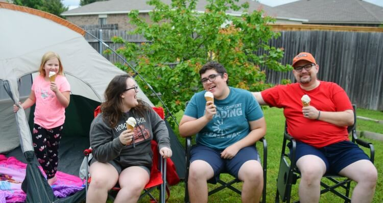 Three kids and dad being silly in the backyard and eating ice cream.
