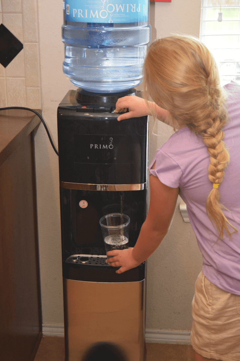A little girl refilling her cup at the Primo Water Dispenser.