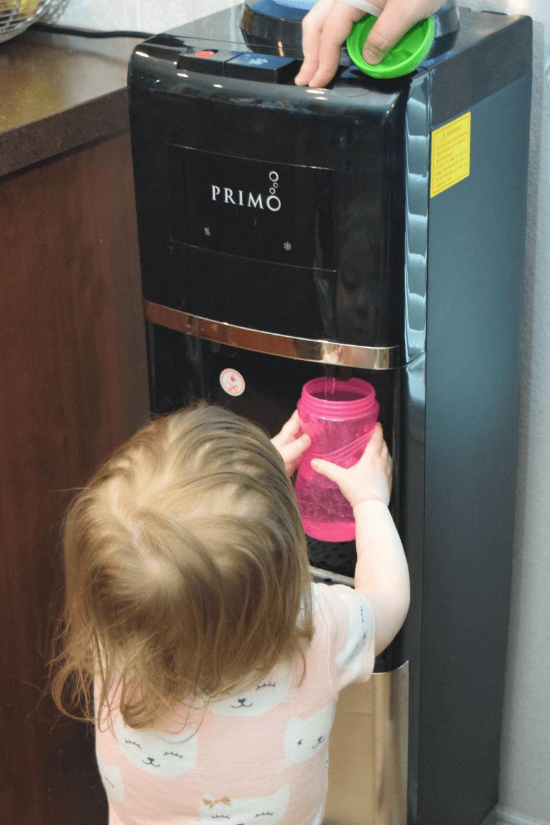A toddler filling her sippy cup at the Primo Water Dispenser