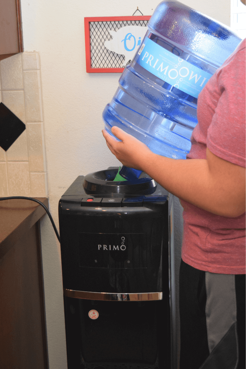Loading the water bottle onto the Primo Water Dispenser