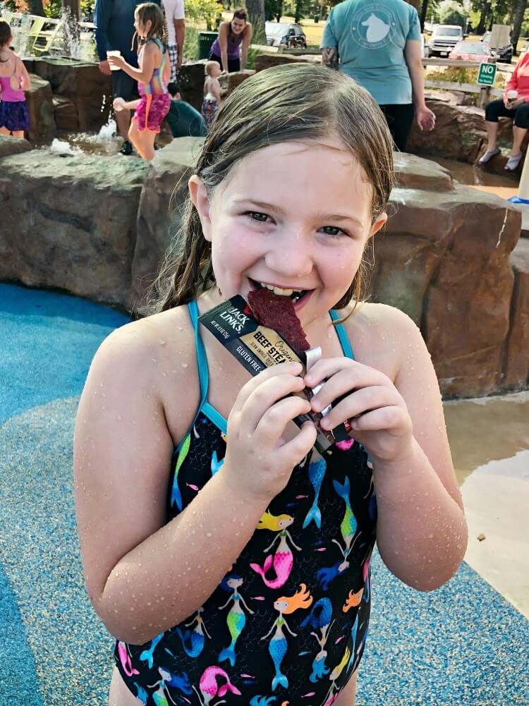 Tween eating a Jack Link's Bar at the splash pad.